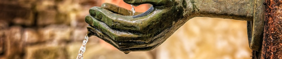 Water running over the hands of a statue.